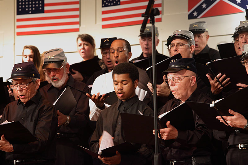 Joshua Johnson (front row center), then a high school sophomore and one of two high school students who auditioned and were accepted as members of the RCS, sings with the chorus during their Spring 2013 Civil War Commemorative Concert.